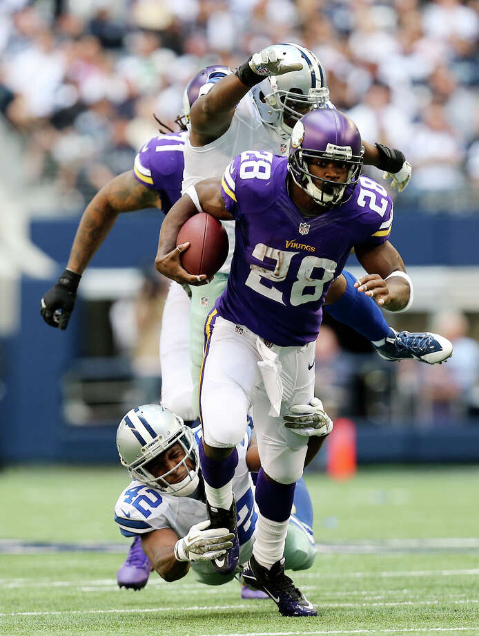 Minnesota Vikings running back Adrian Peterson is chased by Dallas Cowboys' safety Barry Church during the first half at AT&T Stadium, Sunday, Nov. 3, 2013. Photo: Jerry Lara, San Antonio Express-News / ©2013 San Antonio Express-News