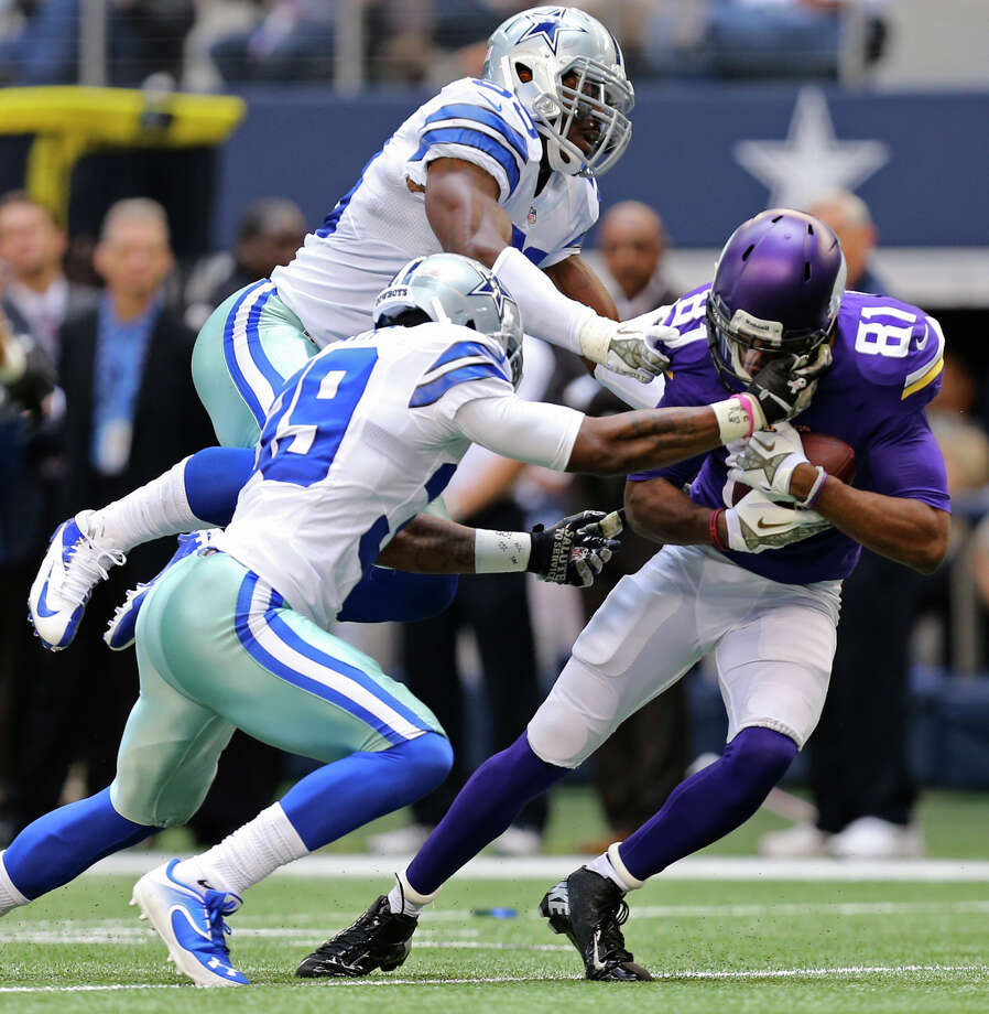 Minnesota Vikings wide receiver Jerome Simpson is brought down by Dallas Cowboys' Brandon Carr, front and Ernie Sims during the first half at AT&T Stadium, Sunday, Nov. 3, 2013. Photo: Jerry Lara, San Antonio Express-News / ©2013 San Antonio Express-News