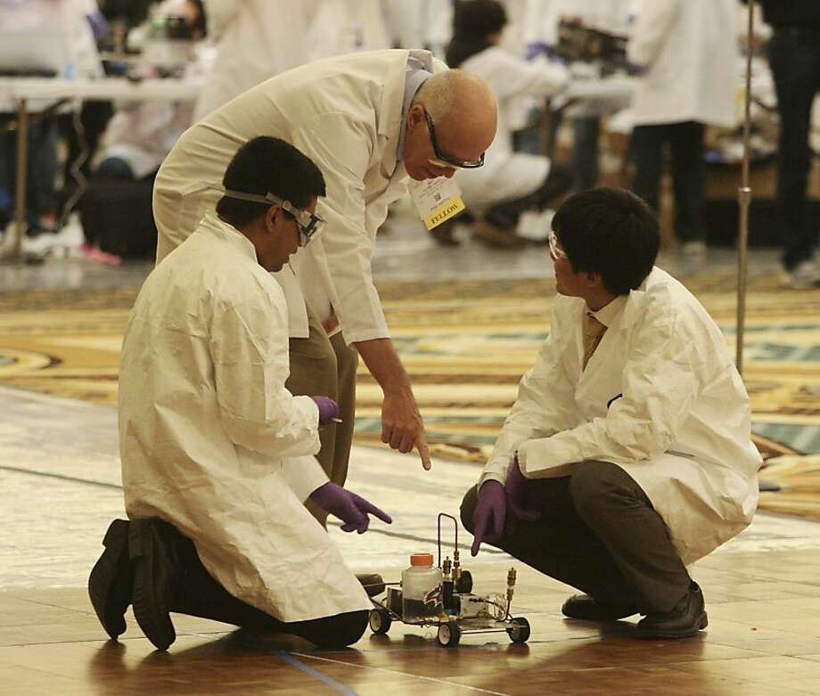 A judge, right, shows Mohammed Rahman (left) and Weida Zhang of Stony Brook University where to place their car at the starting line in the Chem-E-Car Competition at the Hilton in Union Square in San Francisco on Sunday. Photo: Raphael Kluzniok, The Chronicle