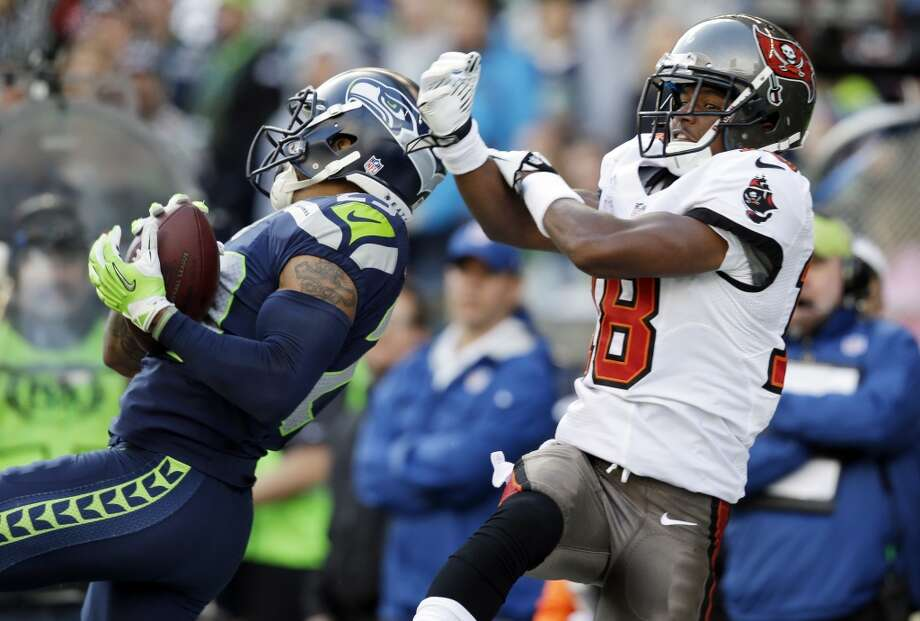 Seattle Seahawks free safety Earl Thomas, left, makes a catch in front of Tampa Bay Buccaneers wide receiver Skye Dawson, right, but was penalized for defensive pass interference on the play, in the first half of an NFL football game Sunday, Nov. 3, 2013, in Seattle. (AP Photo/Elaine Thompson) Photo: AP
