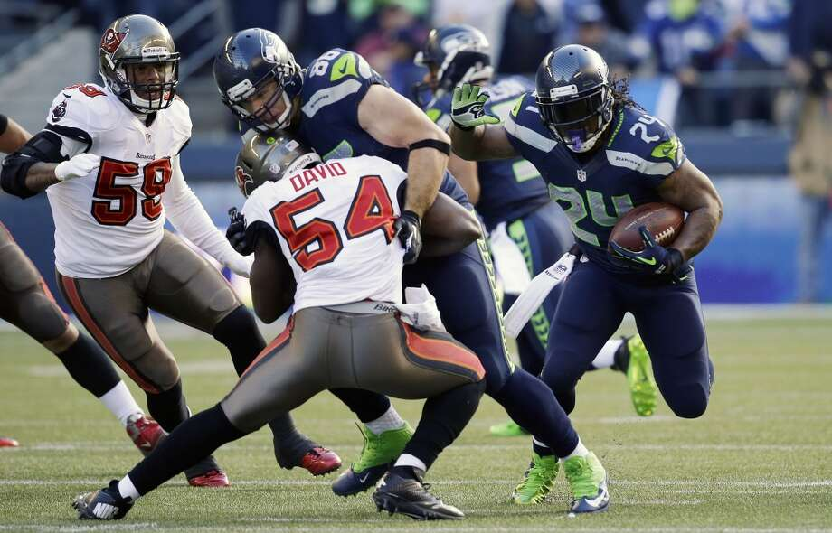 Seattle Seahawks running back Marshawn Lynch, right, rushes as Tampa Bay Buccaneers' Lavonte David (54) is blocked by Seattle Seahawks tight end Zach Miller (86) in the first half of an NFL football game Sunday, Nov. 3, 2013, in Seattle. (AP Photo/Elaine Thompson) Photo: ASSOCIATED PRESS