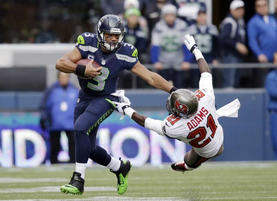 Seattle Seahawks quarterback Russell Wilson (3) pushes off of Tampa Bay Buccaneers' Michael Adams on a long run to set up a touchdown late in the first half of an NFL football game Sunday, Nov. 3, 2013, in Seattle. (AP Photo/Elaine Thompson) Photo: AP