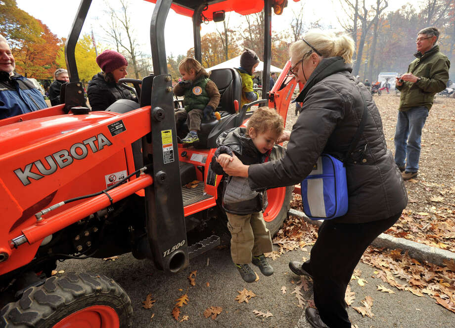 David Dine, 3, is helped off an excavator by his mom, Deborah Dine, during the touch-a-truck portion of the sixth annual Stamford Charity Chili Cookoff at the Stamford Museum and Nature Center in Stamford, Conn., on Sunday, Nov. 3, 2013. Photo: Jason Rearick / Stamford Advocate