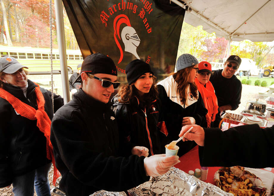 "Stamford High School Marching Band member Brian Roman hands out the band's ""Rancher's Spicy Pinto Bean and Chicken Chili"" during the sixth annual Stamford Charity Chili Cookoff at the Stamford Museum and Nature Center in Stamford, Conn., on Sunday, Nov. 3, 2013. Photo: Jason Rearick / Stamford Advocate"