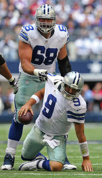 Dallas Cowboys quarterback Tony Romo is helped by tackle Doug Free after a sack during the first half against the Minnesota Vikings at AT&T Stadium, Sunday, Nov. 3, 2013. Photo: Jerry Lara, San Antonio Express-News / ©2013 San Antonio Express-News