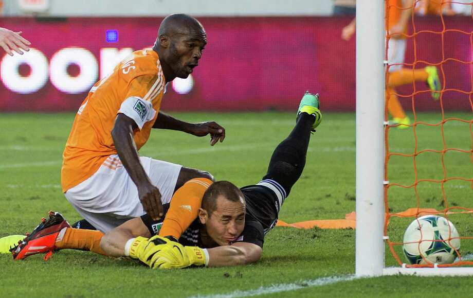 Houston Dynamo forward Omar Cummings beats New York Red Bulls goalkeeper Luis Robles for the equalizer in the second minute of stoppage time of an MLS soccer Eastern Conference Semifinal playoff match on Sunday, Nov. 3, 2013, at BBVA Compass Stadium in Houston. The first leg game ended 2-2. Photo: Smiley N. Pool, Houston Chronicle / © 2013  Houston Chronicle