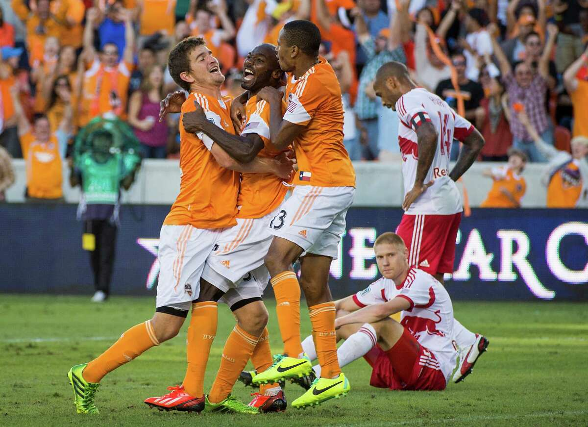 Houston Dynamo forward Omar Cummings, center, celebrates with Bobby Boswell and Ricardo Clark after scoring for the equalizer in the second minute of stoppage time of an MLS soccer Eastern Conference Semifinal playoff match against the New York Red Bulls on Sunday, Nov. 3, 2013, at BBVA Compass Stadium in Houston. The game ended 2-2.