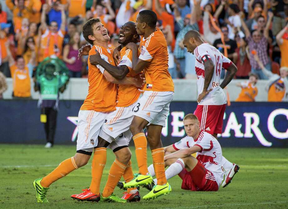 Houston Dynamo forward Omar Cummings, center, celebrates with Bobby Boswell and Ricardo Clark after scoring for the equalizer in the second minute of stoppage time of an MLS soccer Eastern Conference Semifinal playoff match against the New York Red Bulls on Sunday, Nov. 3, 2013, at BBVA Compass Stadium in Houston. The game ended 2-2. Photo: Smiley N. Pool, Houston Chronicle / © 2013  Houston Chronicle
