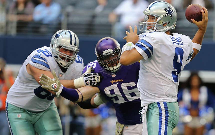 Dallas Cowboys' quarterback Tony Romo looks to pass as tackle Doug Free tries to contain Minnesota V