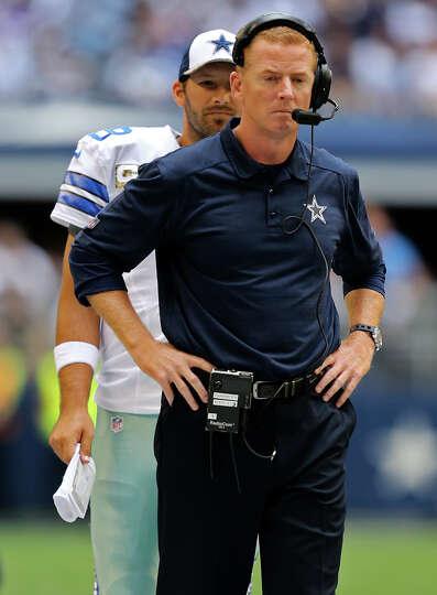 Dallas Cowboys quarterback Tony Romo walks to talk with head coach Jason Garrett during the first