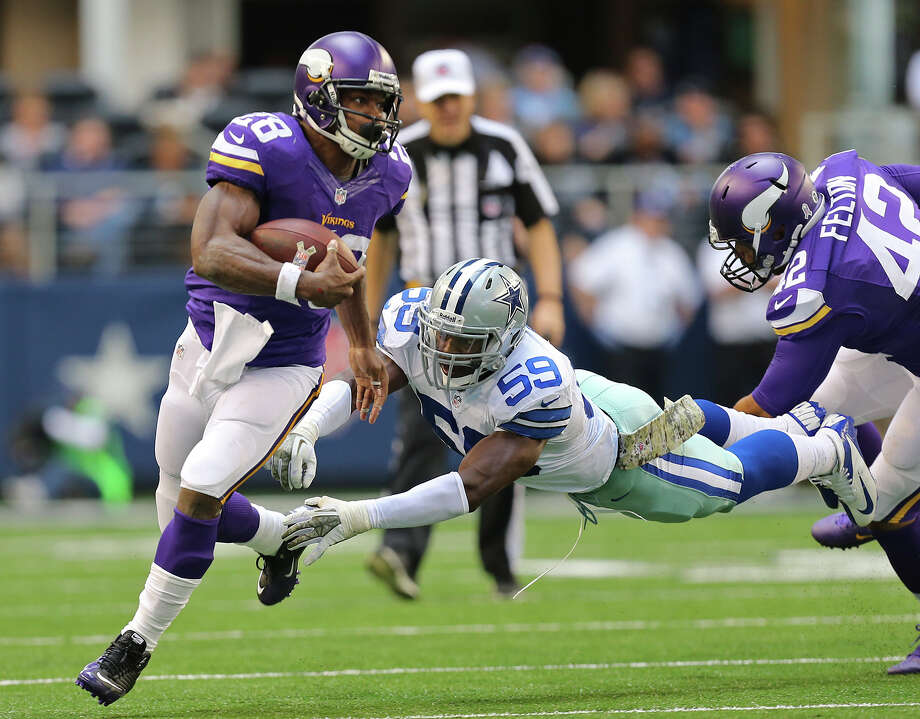 Dallas Cowboys' linebacker Ernie Sims tries to tackle Minnesota Vikings' running back Adrian Peterson during the first half at AT&T Stadium, Sunday, Nov. 3, 2013. Photo: Jerry Lara, San Antonio Express-News / ©2013 San Antonio Express-News
