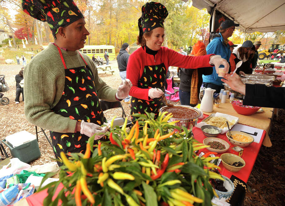 "Rama Kumanduri, left, and his wife, Cristina Romero, serve up their chili titled ""Chile con Pasion"" during the sixth annual Stamford Charity Chili Cookoff at the Stamford Museum and Nature Center in Stamford, Conn., on Sunday, Nov. 3, 2013. Photo: Jason Rearick / Stamford Advocate"