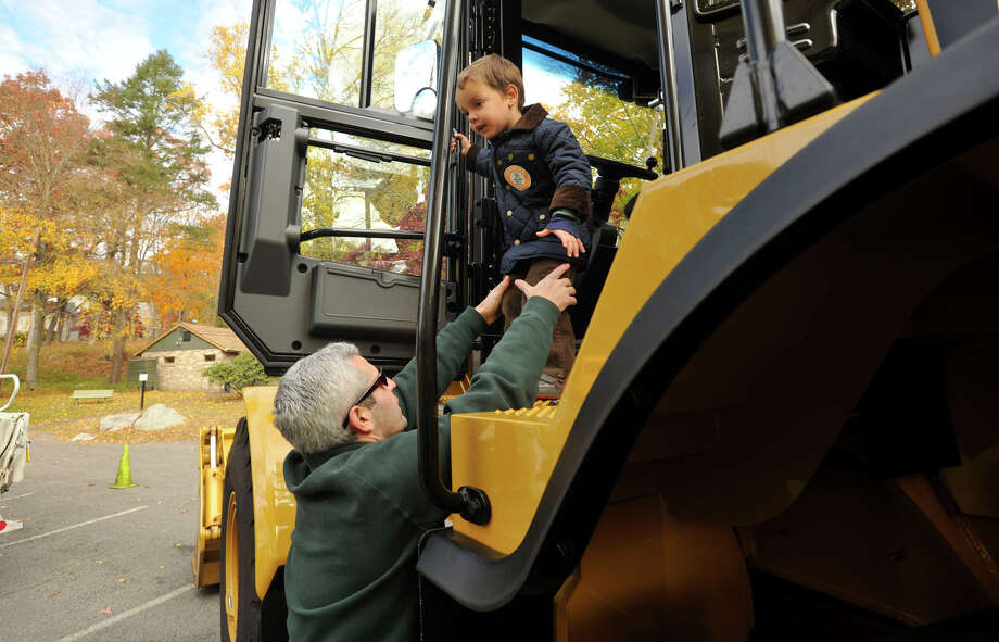 Adam Wolfman helps his son, Noah, off of a large excavator during the sixth annual Stamford Charity Chili Cookoff at the Stamford Museum and Nature Center in Stamford, Conn., on Sunday, Nov. 3, 2013. Photo: Jason Rearick / Stamford Advocate