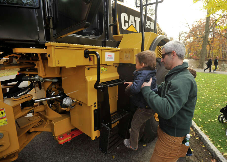 Adam Wolfman helps his son, Noah, onto a large excavator during the sixth annual Stamford Charity Chili Cookoff at the Stamford Museum and Nature Center in Stamford, Conn., on Sunday, Nov. 3, 2013. Photo: Jason Rearick / Stamford Advocate