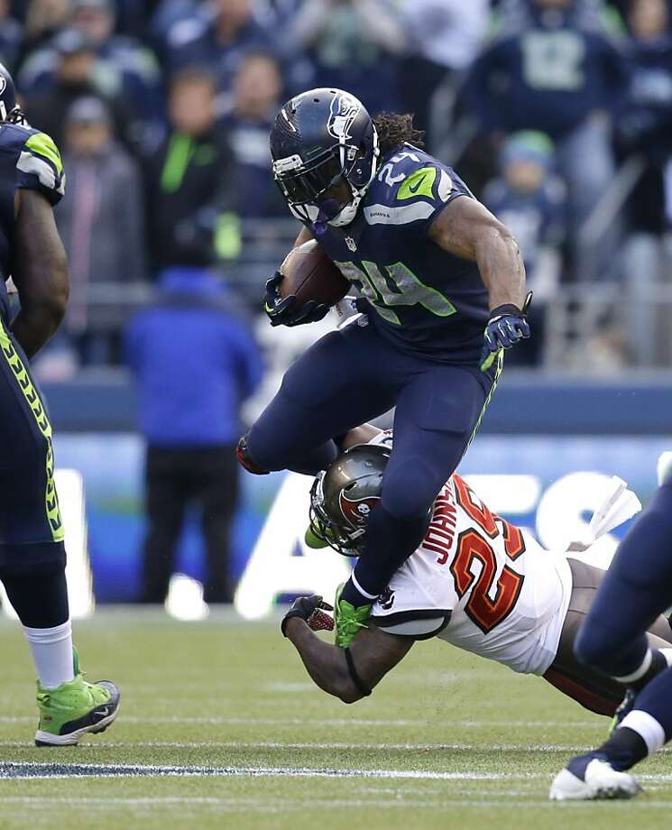 Seattle's Marshawn Lynch, who ran for 125 yards, tries to elude a tackle attempt by Tampa Bay's Leonard Johnson. Photo: Elaine Thompson, Associated Press