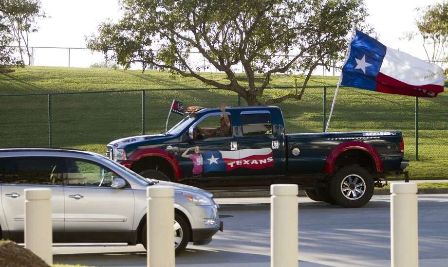 A Texans fan waves from his truck as he drives along Kirby Drive before an NFL football game against the Indianapolis Colts at Reliant Stadium, Sunday, Nov. 3, 2013, in Houston. (Cody Duty / Houston Chronicle) Photo: Cody Duty, Houston Chronicle