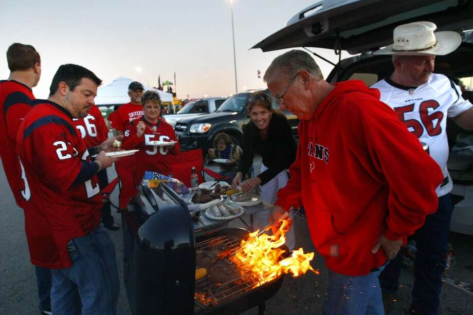 "Alvin Kneisler flips rib eyes on the grill as he tailgates with friends and family before an NFL football game against the Indianapolis Colts at Reliant Stadium, Sunday, Nov. 3, 2013, in Houston. ""Wish we had one every week,"" he said of the night game. ""I like the longer time to tailgate. Noon games are tough to tailgate, too early."" (Cody Duty / Houston Chronicle) Photo: Cody Duty, Houston Chronicle"