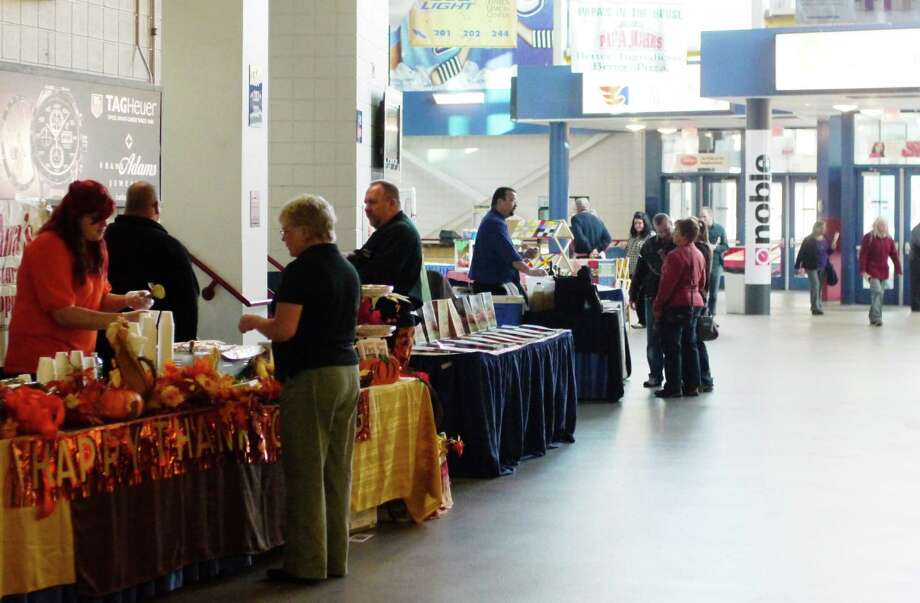 Visitors look over the different vendor's tables at the  'Live Life Local' Indoor Farmer's Market at the Times Union Center on Sunday, Nov. 3, 2013 in Albany, NY.  The event was held to celebrate Albany County's 330th birthday. (Paul Buckowski / Times Union) Photo: Paul Buckowski / 00024099A
