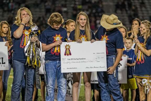 Jacki Dowling, the wife of HFD Capt. William Dowling, reacts after receiving a check for $80,000 at halftime during the school's homecoming game Oct. 23 from the Klein Oak High school student council.