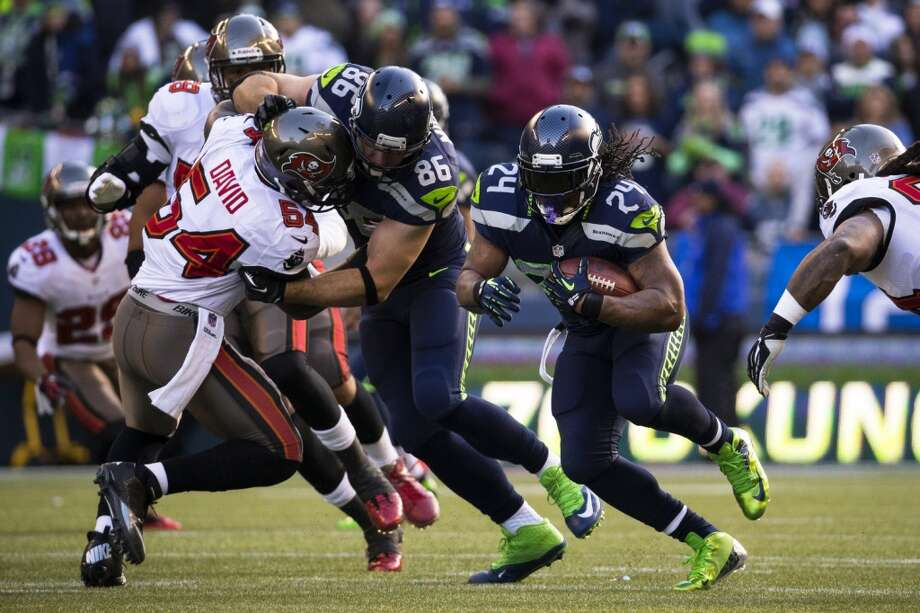 Marshawn Lynch, center right, charges through a hole in Buccaneer defense Sunday, Nov. 3, 2013, at CenturyLink Field in Seattle. The Seahawks beat the Buccaneers 27-24 during overtime in the biggest comeback in franchise history. (Jordan Stead, seattlepi.com) Photo: JORDAN STEAD, SEATTLEPI.COM