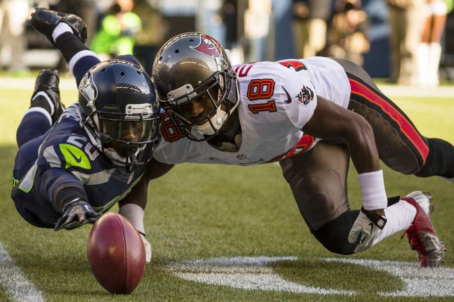 Seahawk Jeremy Lane, left, dives to recover a fumble following Buccaneer Skye Dawson's failed catch of a kicked ball Sunday, Nov. 3, 2013, at CenturyLink Field in Seattle. The Seahawks beat the Buccaneers 27-24 during overtime in the biggest comeback in franchise history. (Jordan Stead, seattlepi.com) Photo: JORDAN STEAD, SEATTLEPI.COM