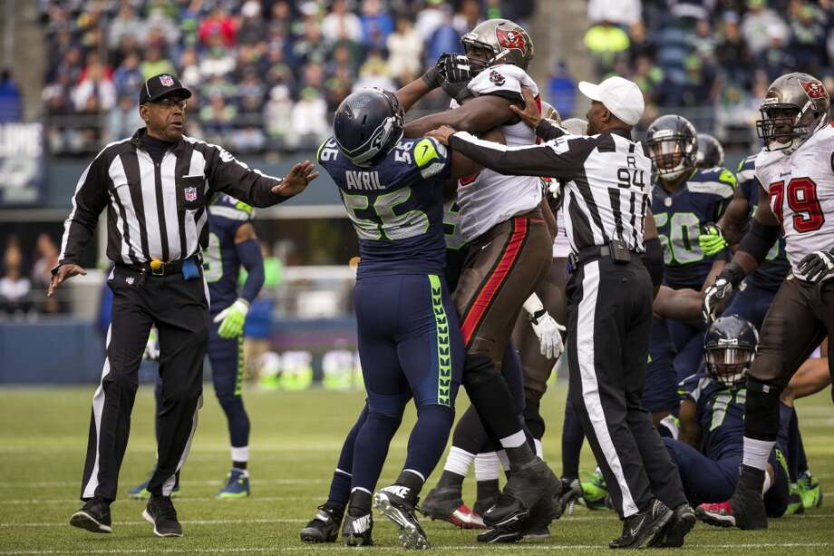 Refs attempt to hold back Seahawk Cliff Avril, center, and Buccaneer Demar Dotson, center right, while they scuffled after a tackle Sunday, Nov. 3, 2013, at CenturyLink Field in Seattle. The Seahawks beat the Buccaneers 27-24 during overtime in the biggest comeback in franchise history. (Jordan Stead, seattlepi.com) Photo: JORDAN STEAD, SEATTLEPI.COM