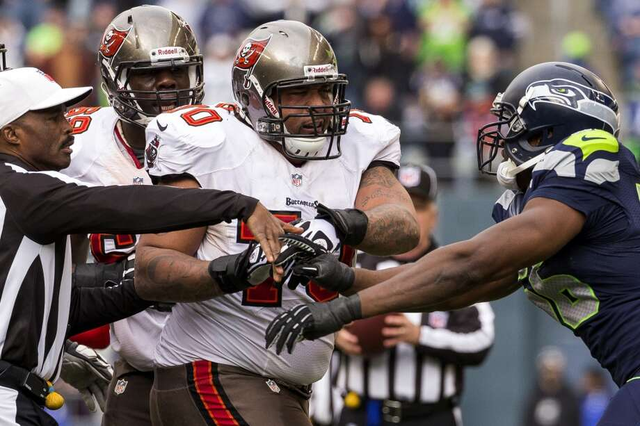 Refs attempt to hold back Seahawk Cliff Avril, right, and Buccaneer Demar Dotson, center, while they scuffled after a tackle Sunday, Nov. 3, 2013, at CenturyLink Field in Seattle. The Seahawks beat the Buccaneers 27-24 during overtime in the biggest comeback in franchise history. (Jordan Stead, seattlepi.com) Photo: JORDAN STEAD, SEATTLEPI.COM