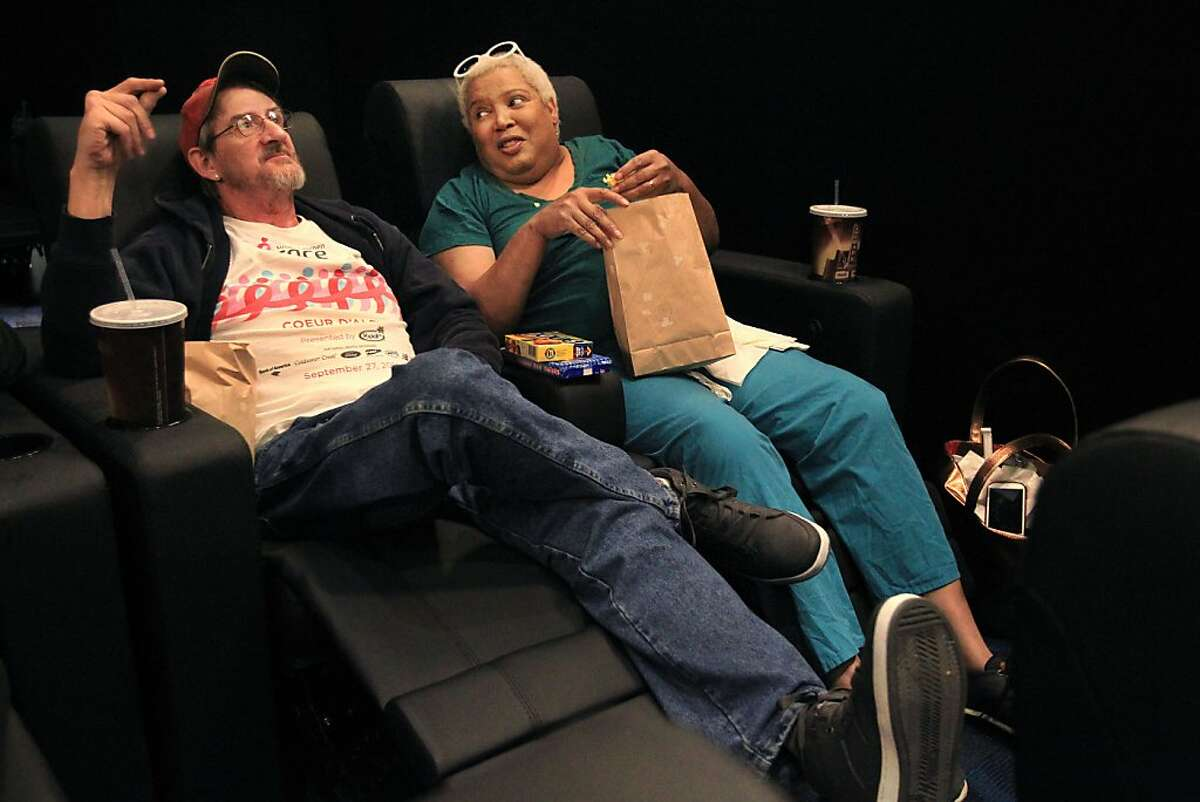 Randy Dolphin and Veronika Fimbres joke around as they wait for 12 Years A Slave to start while using new reclining seats November 1, 2013 during the reopening of the Embarcadero Center Cinema in the One Embarcadero Center in San Francisco, Calif. The newly remodeled cinema features two new screens, a lounge, a beer and wine bar as well as select screens that offer large, reclining seats.