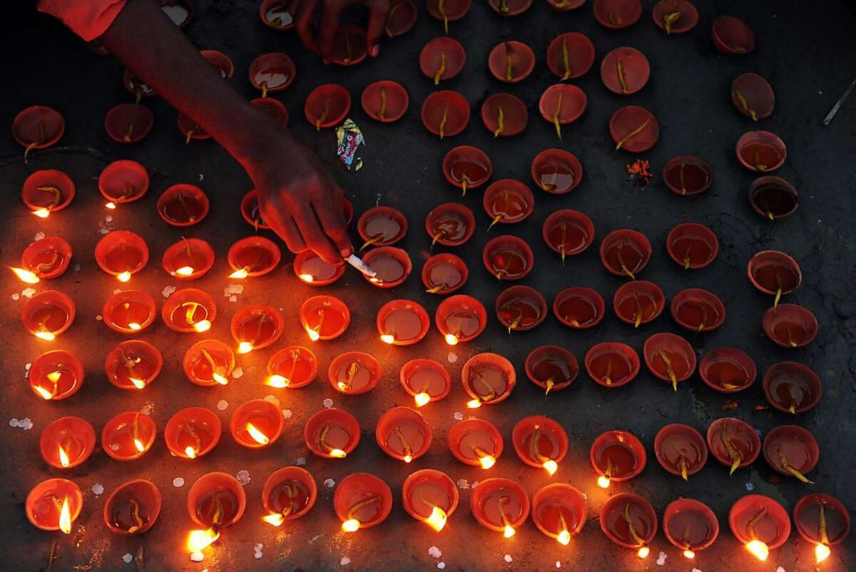 TOPSHOTS An Indian reveller lights earthen lamps during Diwali celebrations in Allahabad on November 3, 2013. Diwali marks the homecoming of the Hindu god Lord Ram after vanquishing the demon king Ravana and symbolises taking people from darkness to light and the victory of good over evil. TOPSHOTS/AFP PHOTO/SANJAY KANOJIASanjay Kanojia/AFP/Getty Images