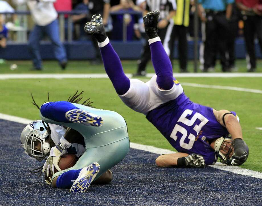 The Cowboys' Dwayne Harris tumbles into the end zone, left, with the winning touchdown pass before Vikings linebacker Chad Greenway (52) can make the play, leaving quarterback Tony Romo and coach Jason Garrett delighted at the last-minute turn of fortune in Sunday's game. Photo: John Rhodes, MBR / Fort Worth Star-Telegram