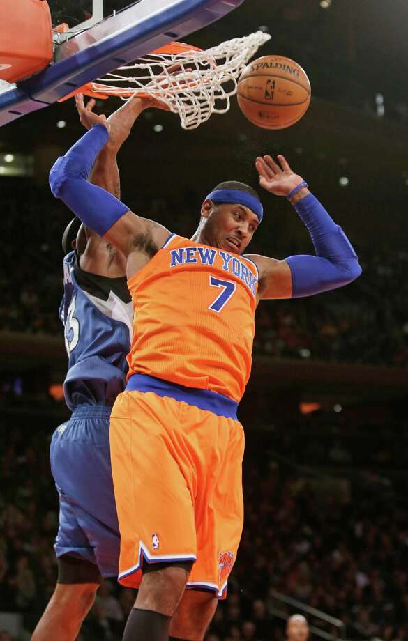 New York Knicks' Carmelo Anthony (7) drives past Minnesota Timberwolves' Dante Cunningham to dunk the ball during the first half of an NBA basketball game Sunday, Nov. 3, 2013, in New York. (AP Photo/Frank Franklin II) ORG XMIT: NYK105 Photo: Frank Franklin II / AP