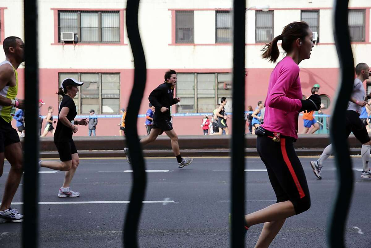Runners, seen through bars on a subway entrance, move up Fourth Avenue in the Brooklyn borough of New York during the New York City Marathon, Sunday, Nov. 3, 2013. (AP Photo/Peter Morgan)