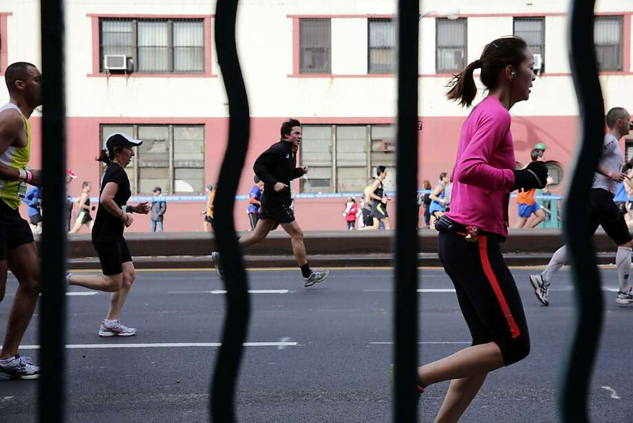 Runners, seen through bars on a subway entrance, move up Fourth Avenue in the Brooklyn borough of New York during the New York City Marathon, Sunday, Nov. 3, 2013. (AP Photo/Peter Morgan) Photo: Peter Morgan, Associated Press