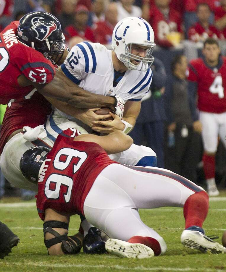 Colts quarterback Andrew Luck (12) is sacked by Texans defensive end J.J. Watt (99) and inside linebacker Joe Mays (53). Photo: Brett Coomer, Houston Chronicle
