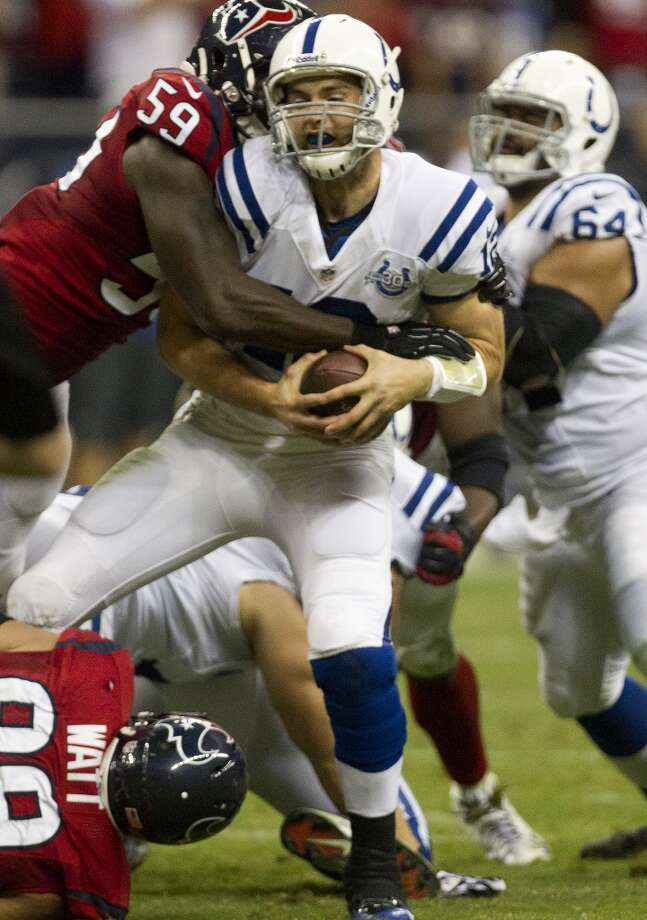 Colts quarterback Andrew Luck (12) is sacked by Texans outside linebacker Whitney Mercilus (59) and defensive end J.J. Watt (99). Photo: Cody Duty, Houston Chronicle