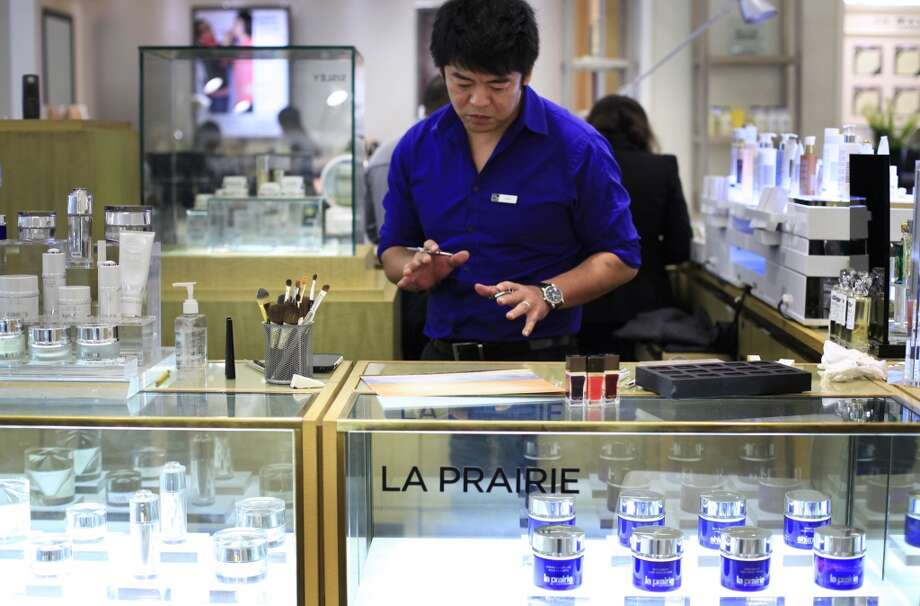 Sing Chang, beauty specialist at Saks Fifth Avenue, steps back for a second to get a different perspective on his all-cosmetic painting at the La Prairie counter in San Francisco, Calf. Photo: The Chronicle