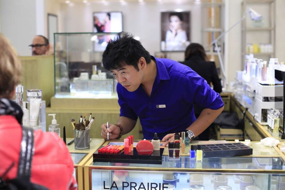 A curious customer walks past as Sing Chang, a beauty specialist at Saks Fifth Avenue, works on one of his all-cosmetic paintings at the La Prairie counter in San Francisco, Calf. Photo: The Chronicle