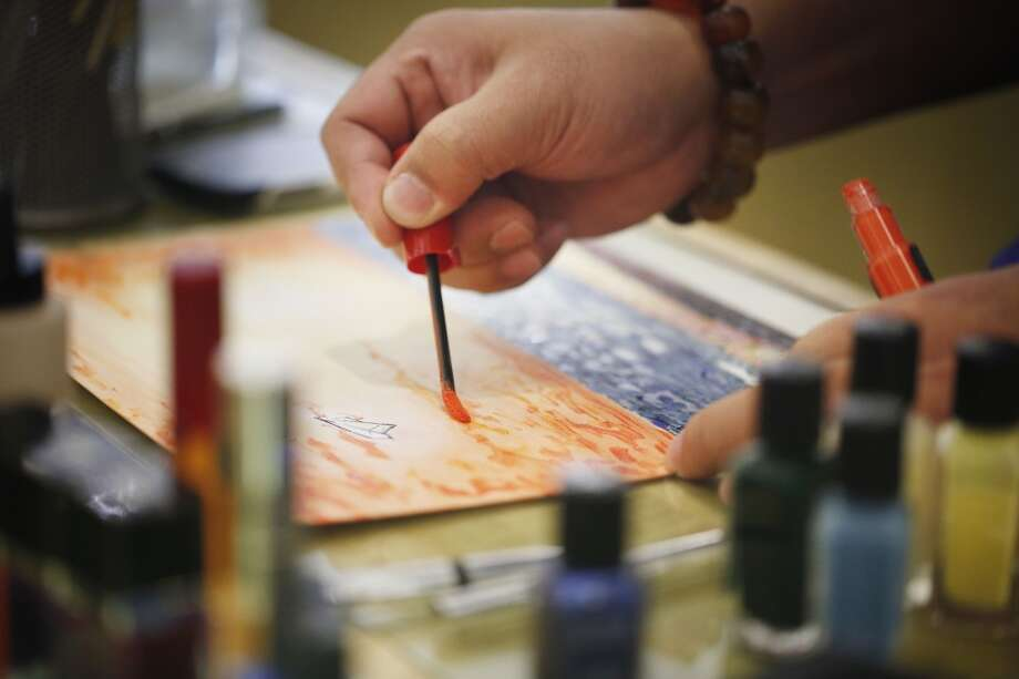 Sing Chang, beauty specialist at Saks Fifth Avenue, add an warm toned eye liner to his all-cosmetic painting at the La Prairie counter in San Francisco, Calf. Photo: The Chronicle