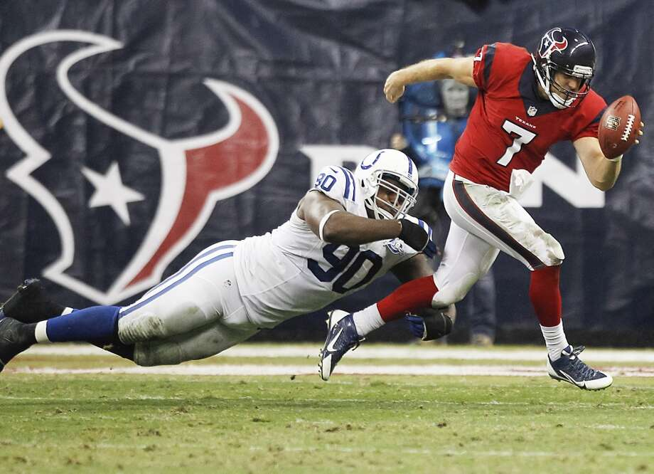 Texans quarterback Case Keenum scrambles away from Colts defensive end Cory Redding. Photo: Brett Coomer, Houston Chronicle
