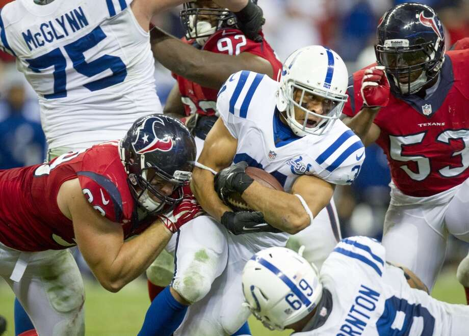 Colts running back Donald Brown holds on to the ball as he's brought down by a host of Texans defenders during the second half. Photo: Cody Duty, Houston Chronicle
