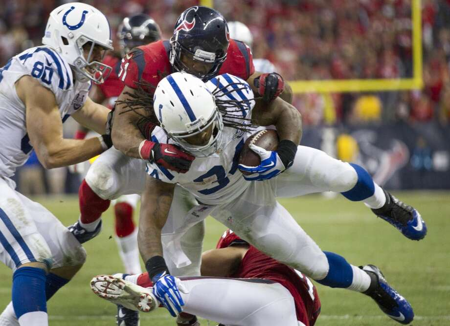 Colts running back Trent Richardson is brought down by Texans linebacker Darryl Sharpton. Photo: Brett Coomer, Houston Chronicle
