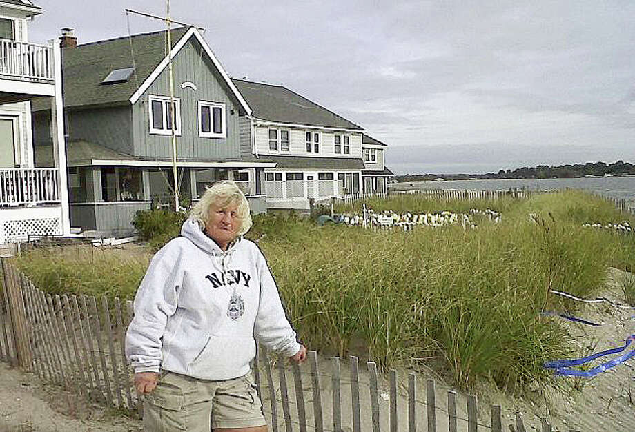Paige Herman, president of the Fairfield Beach Residents Association, on Oct. 16 poses in front of her house on the beach in Fairfield. The association is giving away thousands of plants to encourage residents to create or expand sand dunes, and Herman thinks the little dune in front of her house likely prevented even worse damage than she suffered during Superstorm Sandy. The growing interest in building berms and dunes faces obstacles, including concerns about obstructed views in a swath of land with some of the nation's priciest real estate. Photo: Associated Press / Fairfield Citizen contributed