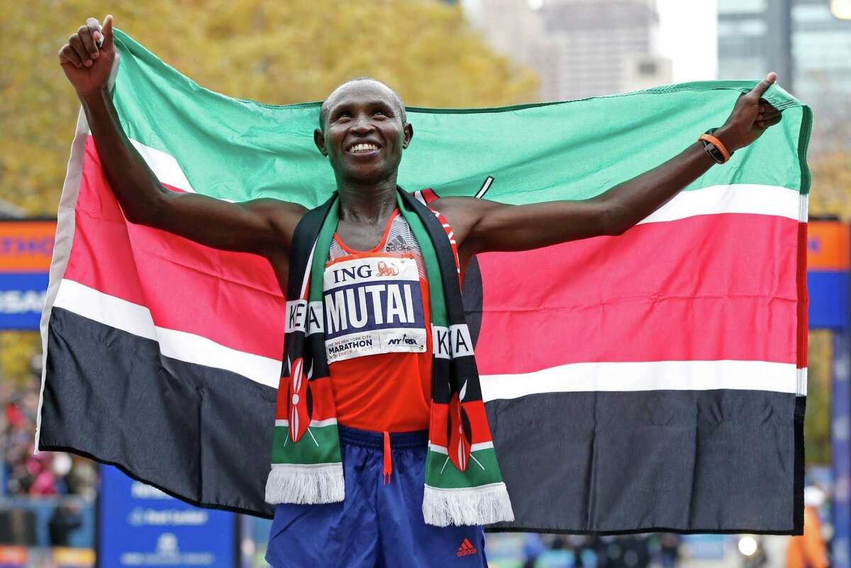 Geoffrey Mutai of Kenya holds the Kenyan flag after winning the men's division of the New York City Marathon, Sunday, Nov. 3, 2013, in New York. (AP Photo/Kathy Willens) ORG XMIT: NYKW108