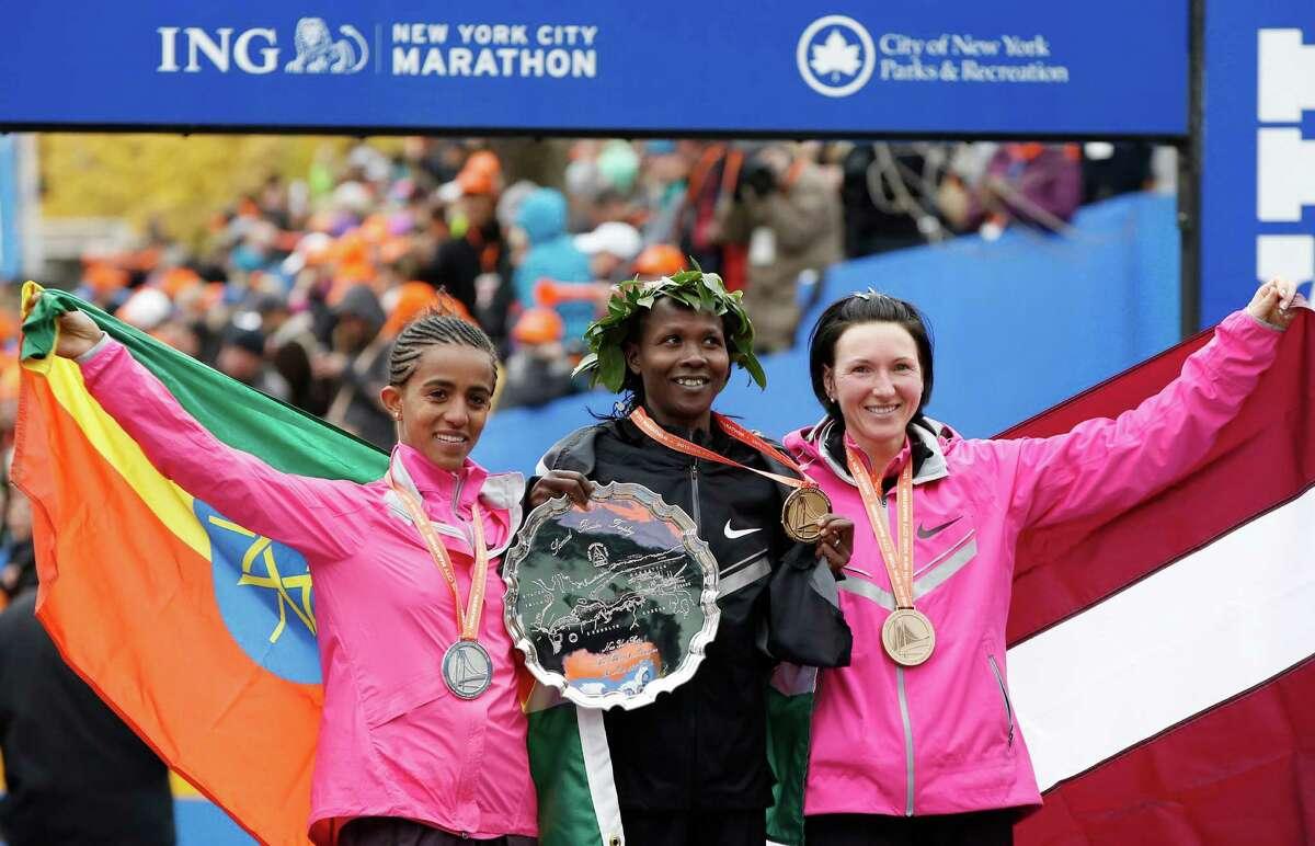 Women's winner Priscah Jeptoo of Kenya, center, second place finisher Buzunesh Deba of Ethiopia, left, and third place finisher Jelena Prokopcuka of Latvia pose after the New York City Marathon, Sunday, Nov. 3, 2013, in New York. (AP Photo/Kathy Willens) ORG XMIT: NYKW118