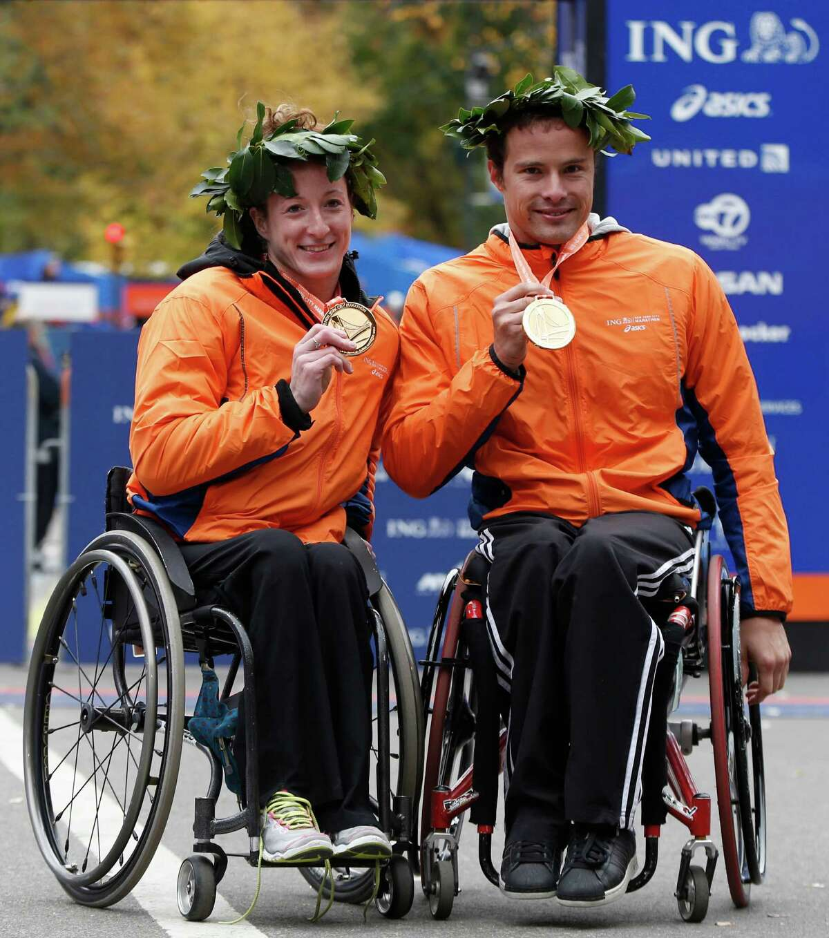 Women's wheelchair winner Tatyana McFadden of Maryland, left, and men's wheelchair winner Marcel Hug of Switzerland pose for photographers after winning their divisions in the New York City Marathon, Sunday, Nov. 3, 2013, in New York. (AP Photo/Kathy Willens) ORG XMIT: NYKW111
