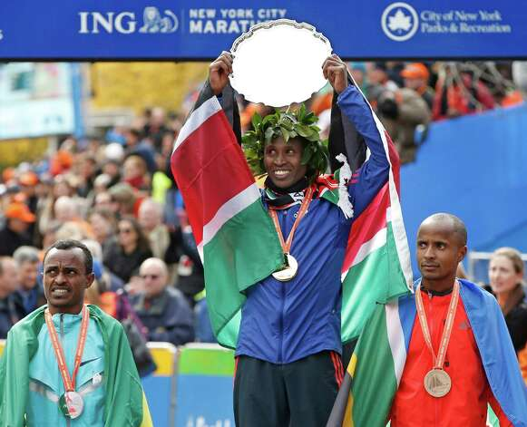 Second place finisher Tsegaye Kebede, left, of Ethiopia, and third-placed Lusapho April, right, of South Africa, flank men's winn