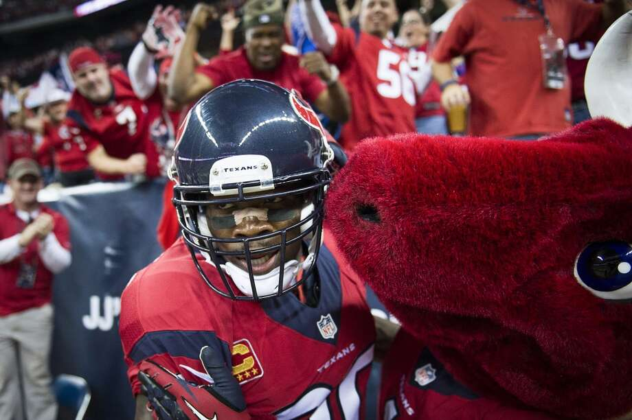 Texans wide receiver Andre Johnson celebrates with the team mascot Toro after catching a 62-yard touchdown pass from Case Keenum during the first quarter. Photo: Smiley N. Pool, Houston Chronicle