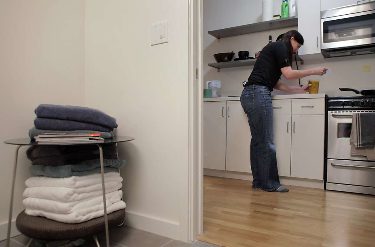 Kayla Smith cooks dinner in her kitchen, which is just feet away from the bathroom in her San Francisco, Calif., apartment on Tuesday, October 29, 2013. Smith moved into the micro apartment when she was hired by Webpass, a San Francisco-based internet company. The tiny space, about 280 square feet is perfect for her lifestyle at the moment, she says, but she still needs to furnish the apartment so it feels less sparse.