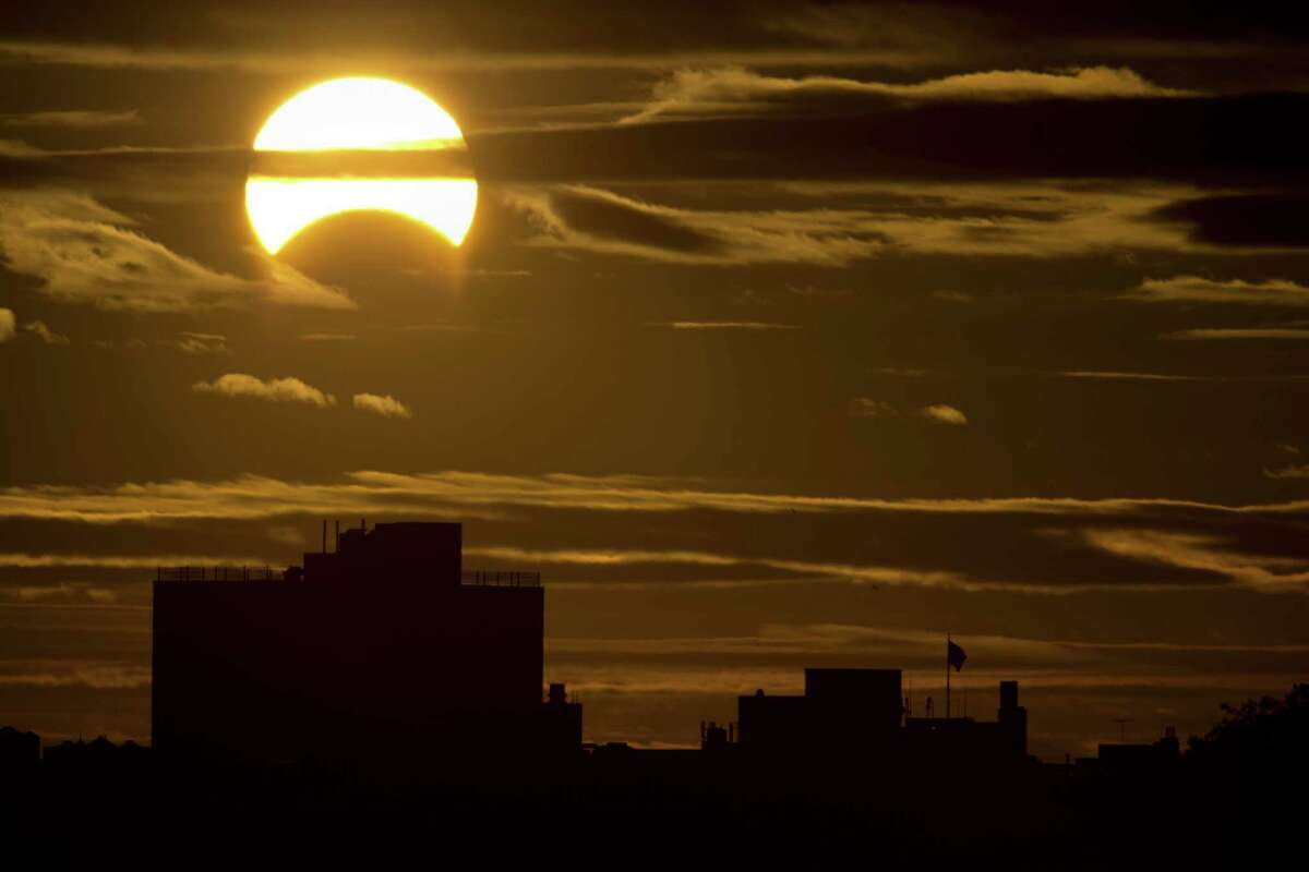 TOPSHOTS A partial Solar eclipse is seen just after sunrise over the Queens borough of New York across the East River on November 3, 2013 in New York. AFP PHOTO/Stan HONDASTAN HONDA/AFP/Getty Images