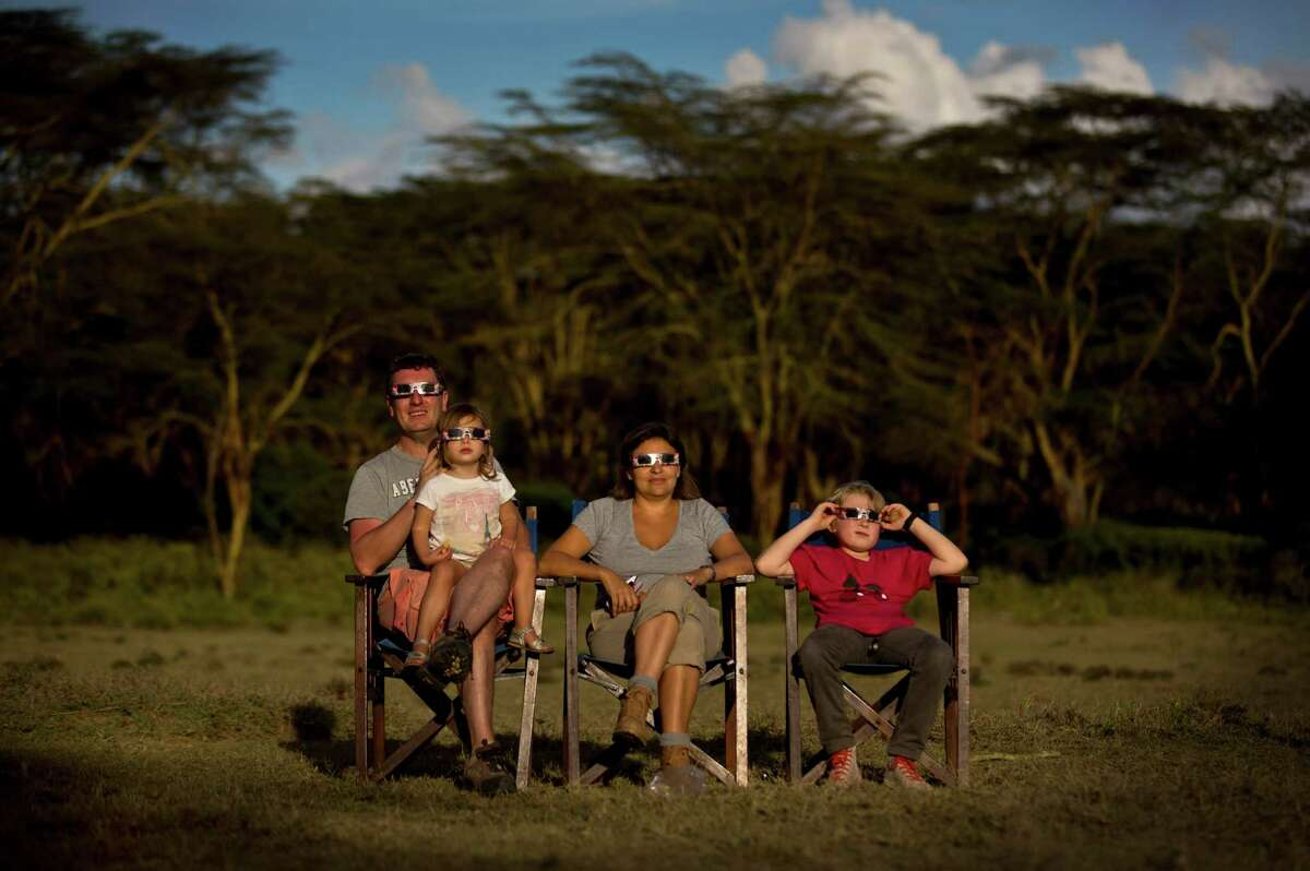 Belgian tourists watch a hybrid solar eclipse from Lake Oloidien near Naivasha in Kenya Sunday, Nov. 3, 2013. A rare solar eclipse swept across parts of the US, Africa and Europe on Sunday with some areas witnessing a total blackout and others experiencing a partial version. (AP Photo/Ben Curtis) ORG XMIT: ABC103